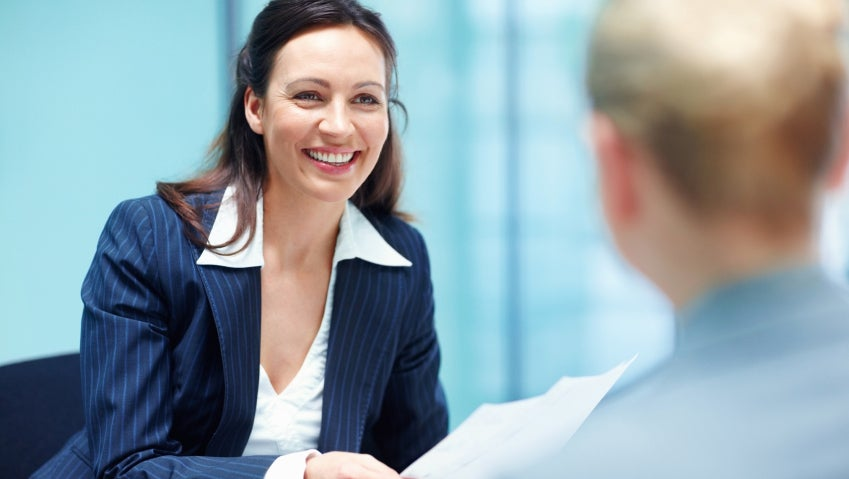 Smiling business woman conversing with executive
